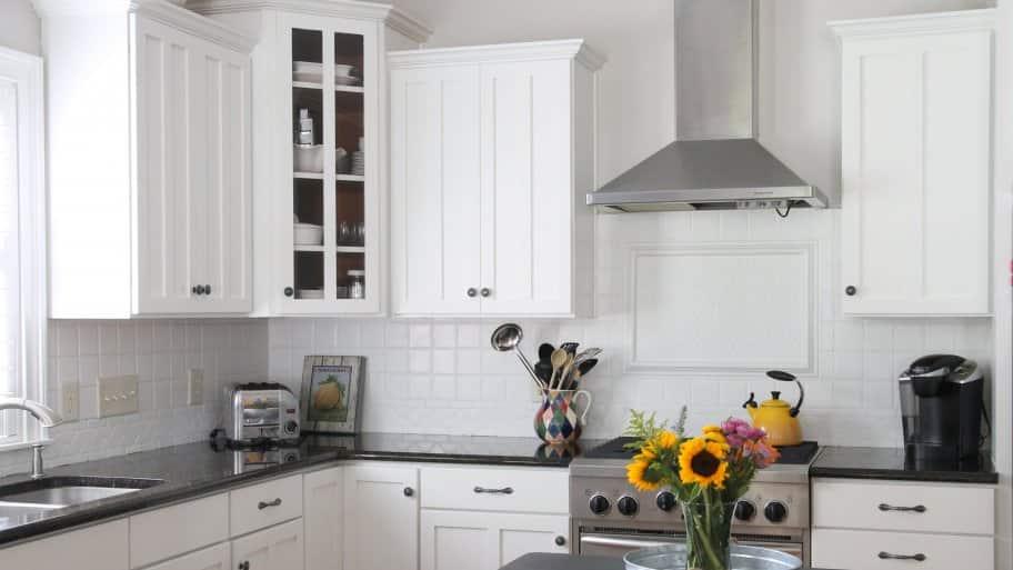 kitchen with white cabinets, white backsplash, dark counters