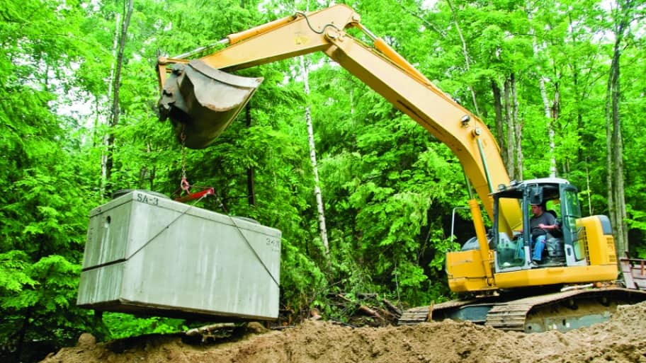 Installing septic tank with excavator at construction site.
