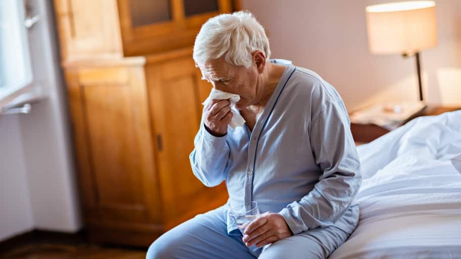 A man sits on the edge of his bed with pneumonia. (Photo by Photo courtesy of iStock)