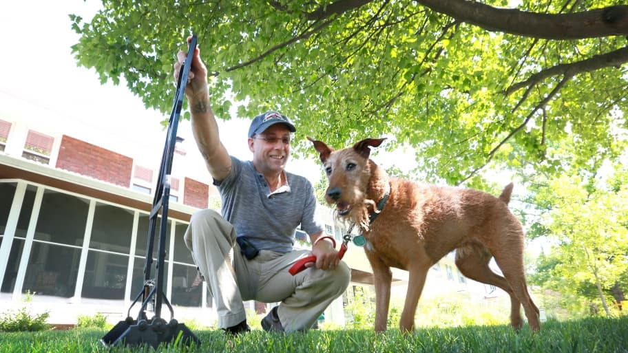 man with dog and pooper scooper