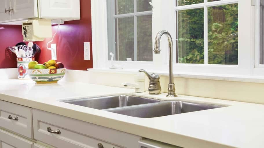 kitchen sink with faucet and cream countertop