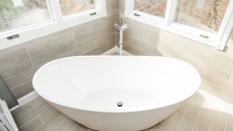 white ceramic bathtub in corner of bathroom with windows above