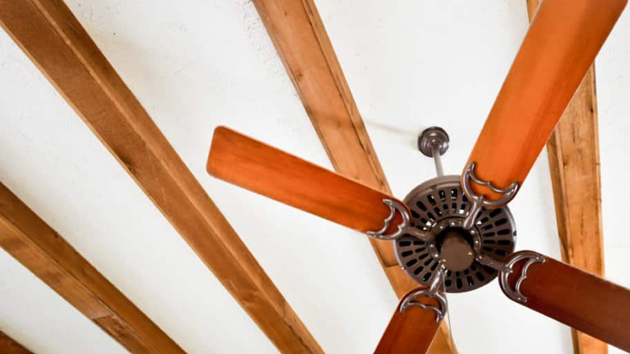 Ceiling fan connected to ceiling with wood beams