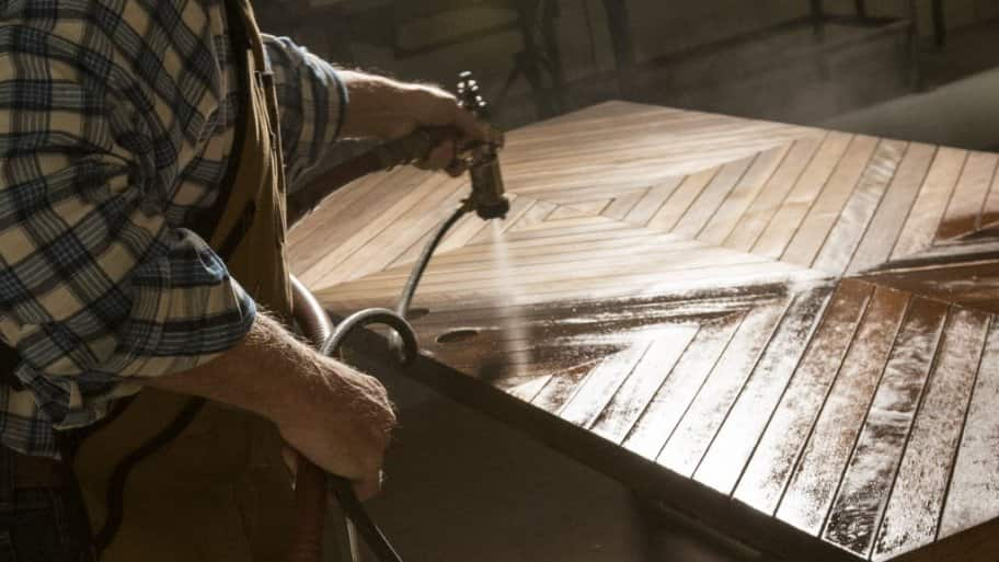 Greg Doublestein of The Front Gate sprays a coat on varnish on a door