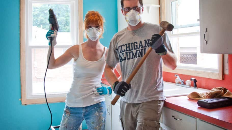 woman and man wearing air filter masks and holding a drill and sledgehammer