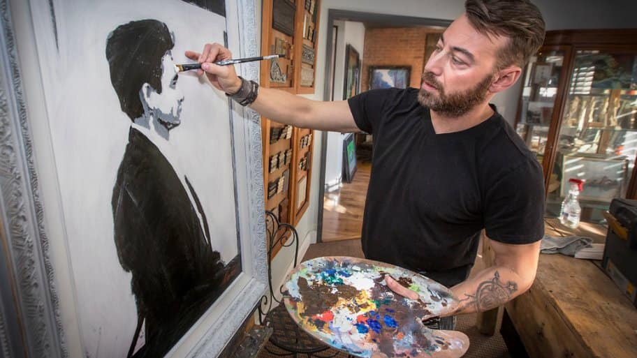 Silver Crow Studios' Sean Sheppard completes a painting of Johnny Cash.