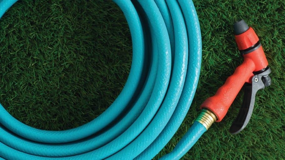 a blue garden hose and sprayer laying on grass