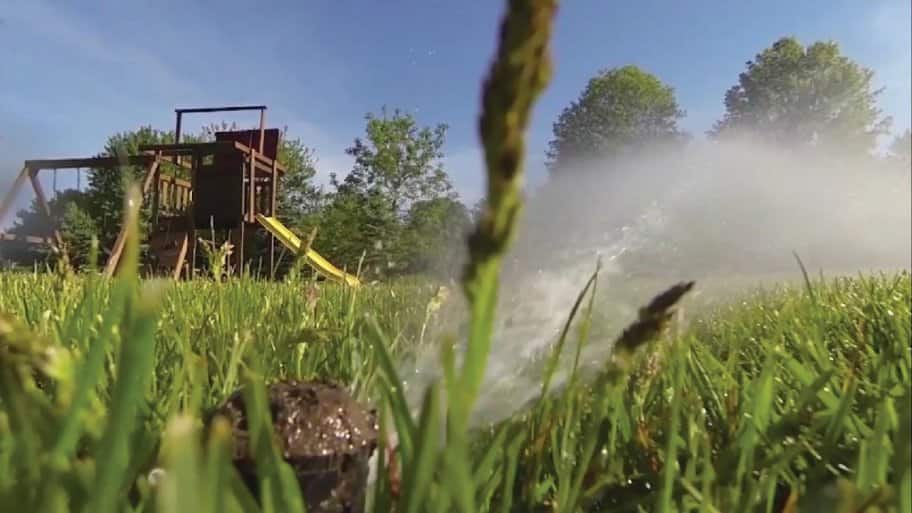 Up close picture of a lawn sprinkler with a small playground with yellow slide in the background