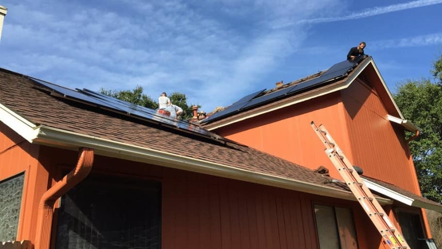 A crew installing solar panels on a roof
