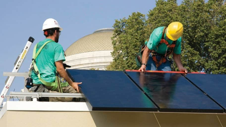 Two men installing solar panels on a rooftop