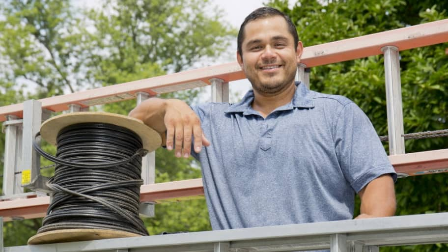 Omar Santiago, owner of Indy Antennas, with a ladder and spool of cable