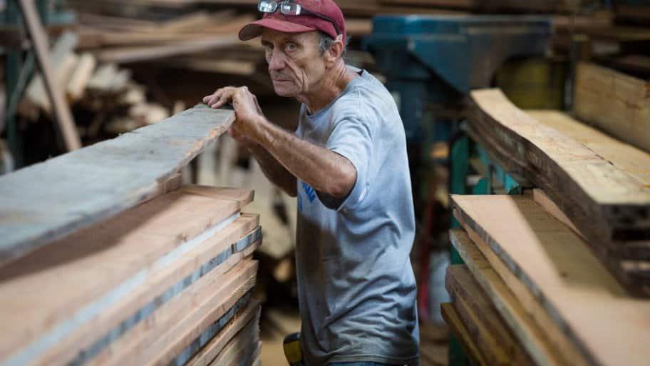 Carpenter surveys reclaimed wood at Southern Pine Co. warehouse in Savannah, Georgia