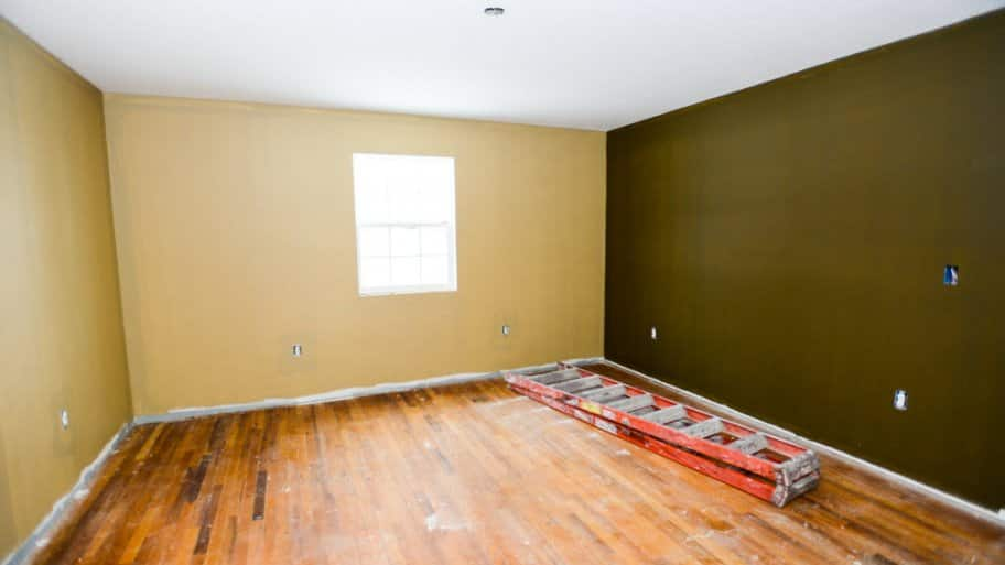 A room with hardwood floor painted yellow on one wall and green on the other