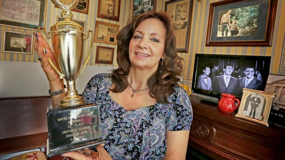 mayberry cafe owner christine borne holding a squad car nationals trophy