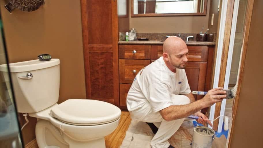 a man painting a bathroom