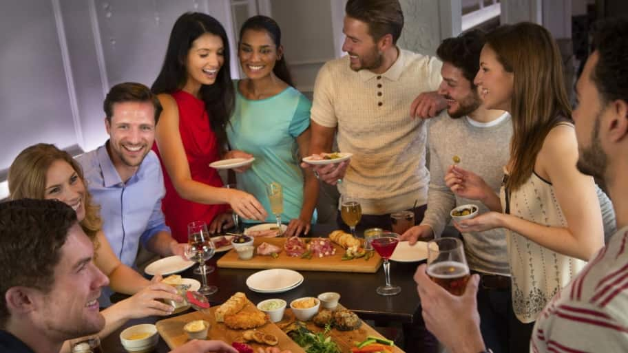 adults eating and drinking at an office party