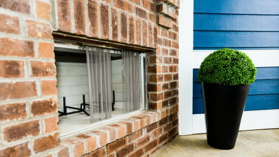 a brick fireplace with a plant nearby