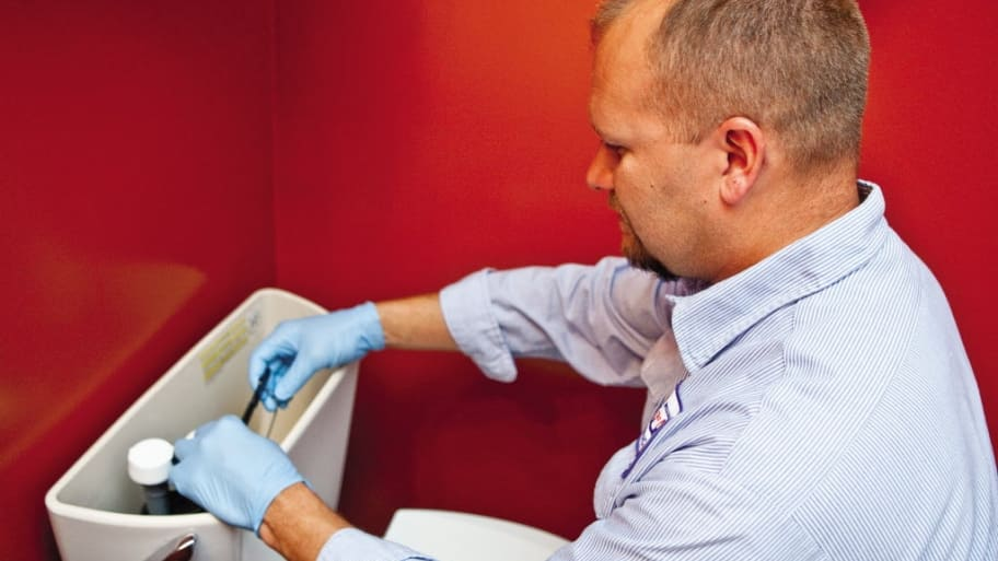 Plumber working on toilet