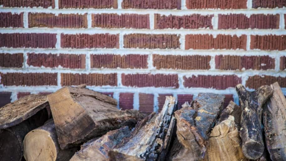 A Brick Wall With Some Firewood