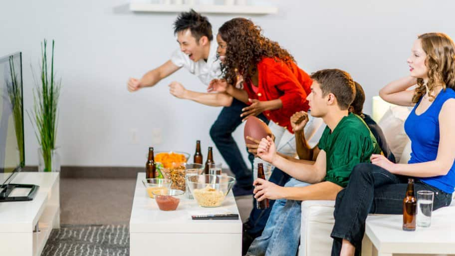 Friends on a couch drinking beer and watching a football game, two up and cheering