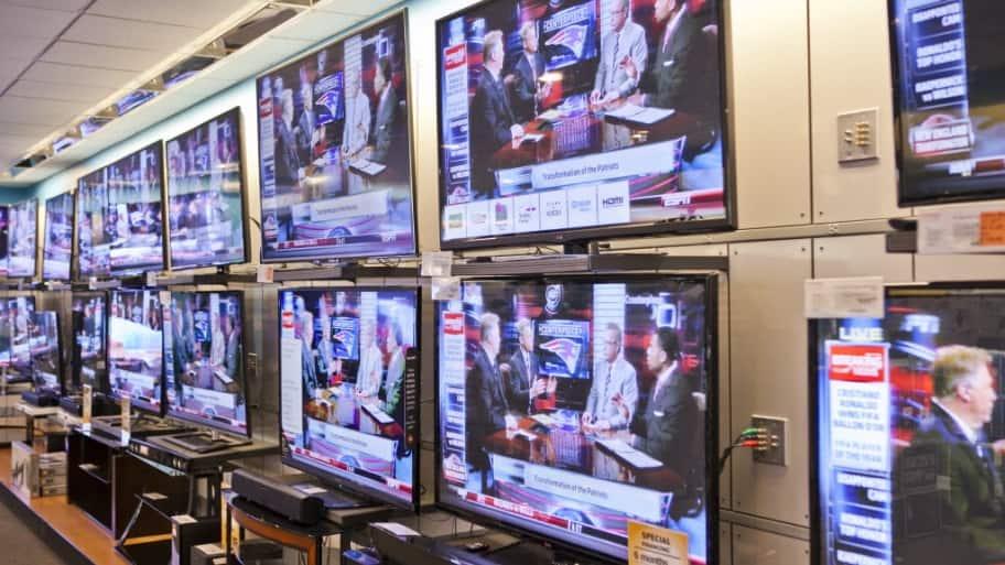 a bunch of flat screen tvs showing espn