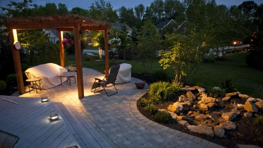 A Back Yard With Gazebo Rocks Trees And Outdoor Lighting