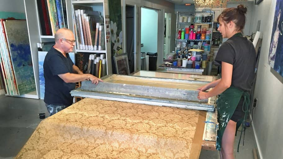 Walter Knabe and assistant Emily McAvoy screen print a roll of gold custom wallpaper