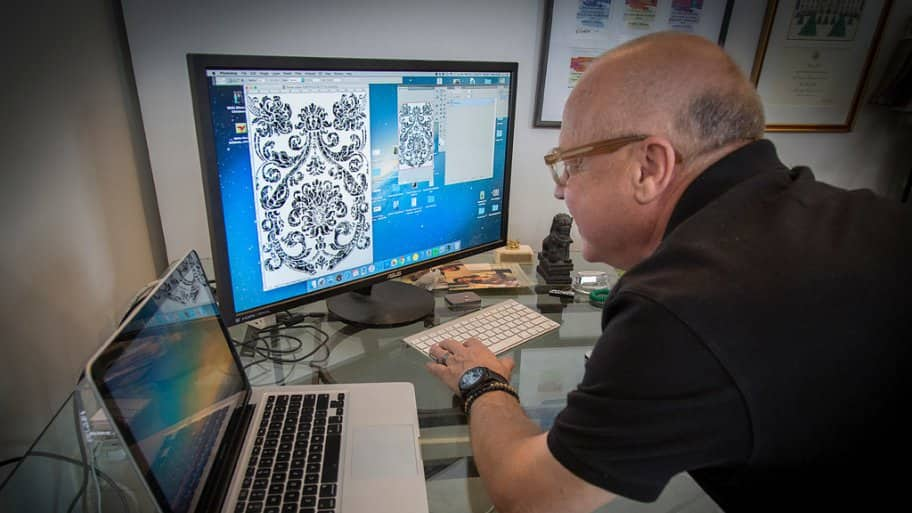 Walter Knabe looking a one of his wallpaper designs on computer