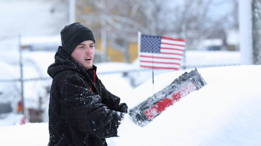 a man shoveling snow off of a car