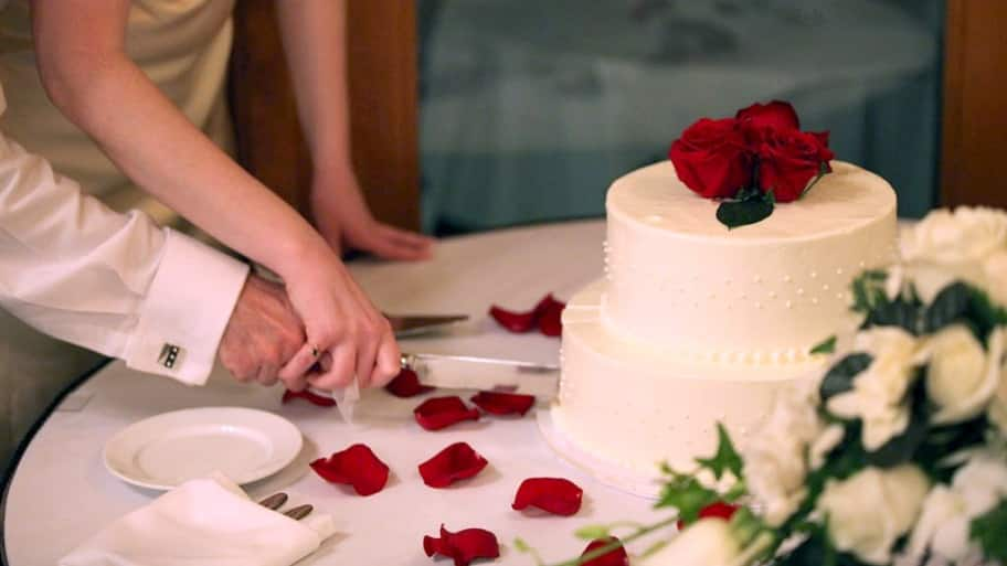 a couple cutting a wedding cake