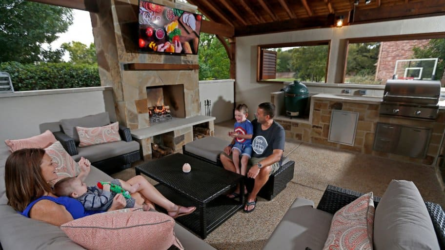 Jack and Samantha Rutty pose for a photograph with their sons Conner and Jaiden inside the covered outdoor kitchen and fireplace at their home in the Dallas/Fort Worth area, Texas. (Photo by Jae S. Lee)