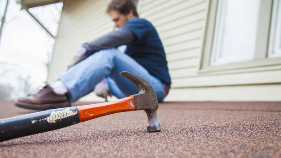 home improvement contractor sitting on roof with hammer