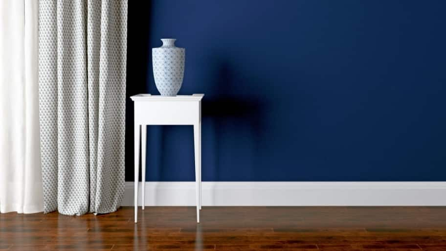Blue Wall White Baseboard In Room Setting
