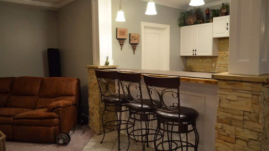 remodeled basement with bar, cabinets and seating area