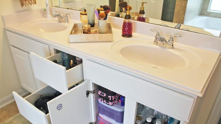 A bathroom counter and cabinet with drawer organizers