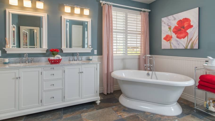 master bathroom with wainscot, double vanity and soaker tub