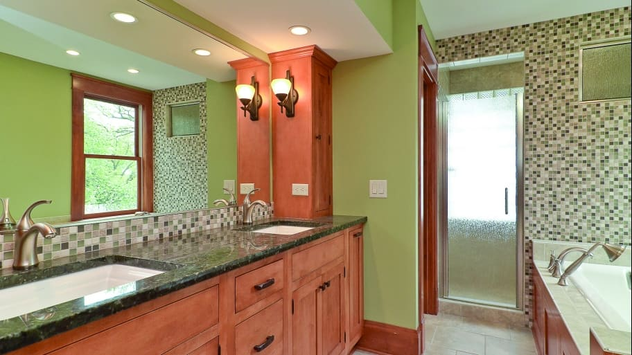 bathroom with green walls, wooden cabinets and marble countertops