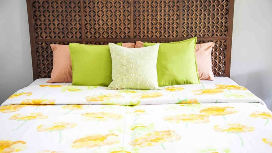 bed with flowery bedspread and decorative pillows