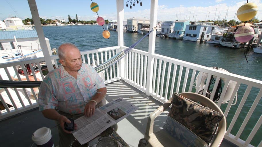 Bob Kelly reading newspaper on houseboat upper deck (Photo by Mike Hentz)