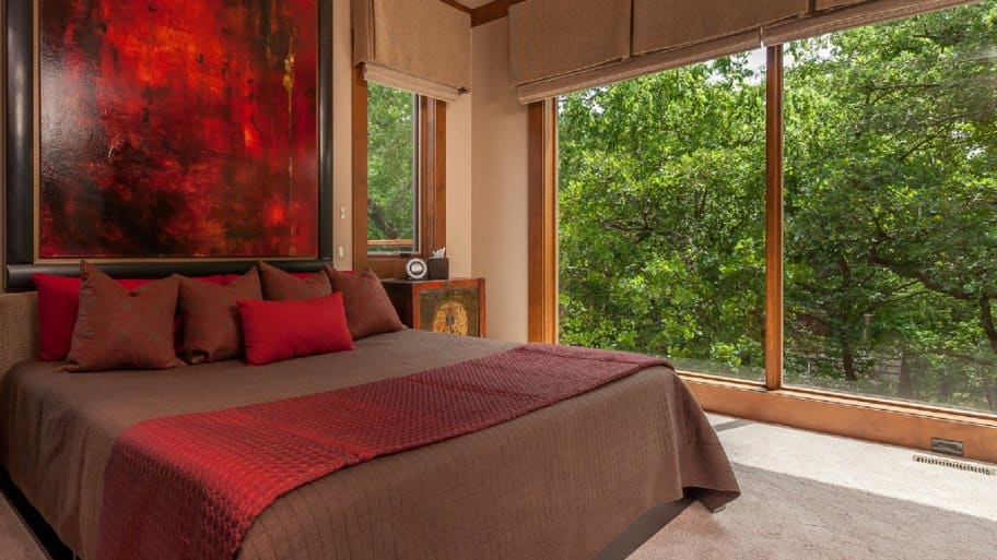 bedroom with big windows and view of woods