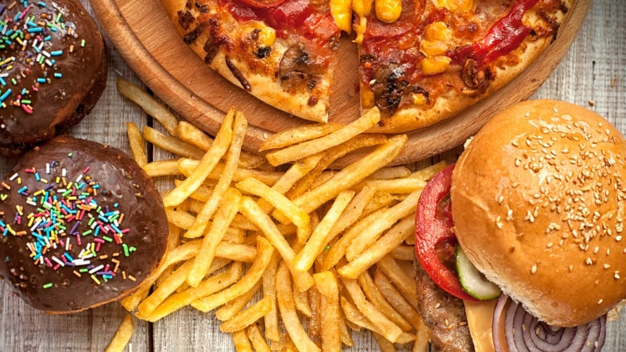Cupackes, pizza, fries and a burger sit temptingly on a table.