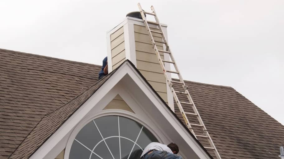 roofer making repairs around window and chimney