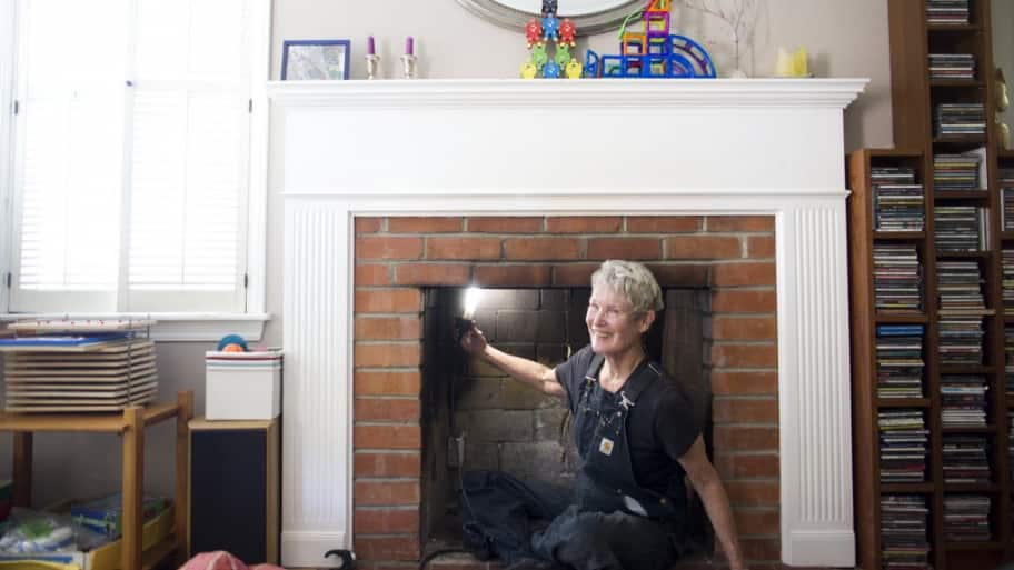 Chimney sweeper in front of a fireplace