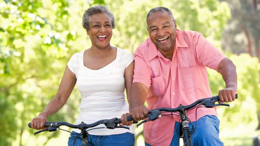 A senior couple enjoy a bicycle ride together.