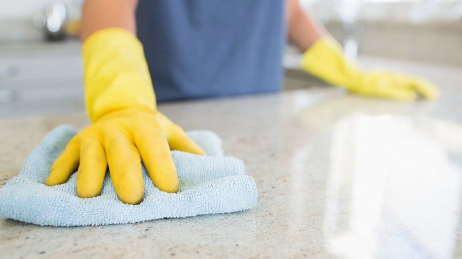 yellow gloved hand using cloth to clean countertop