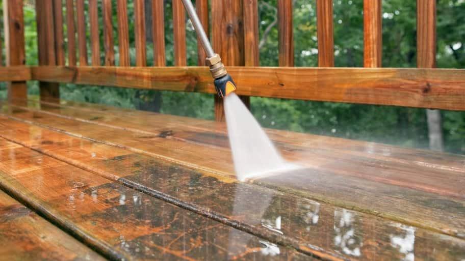 pressure washer spraying wood deck
