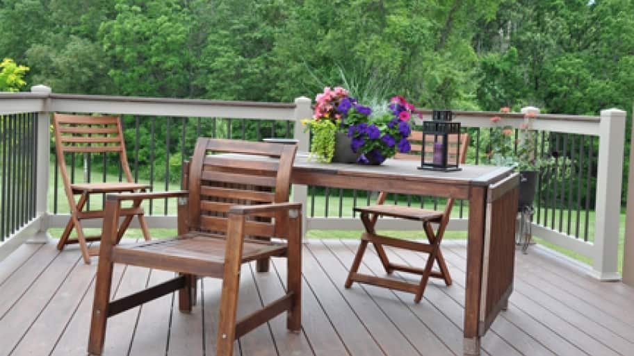 a table set with flowers on a deck overlooking a backyard.