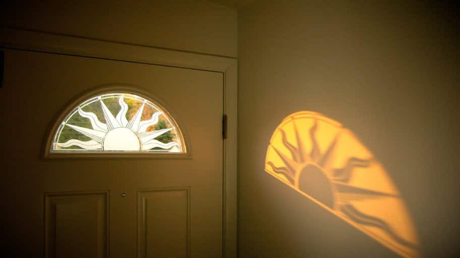 decorative window film shaped as a sun on peephole window of entry. Black Bedroom Furniture Sets. Home Design Ideas
