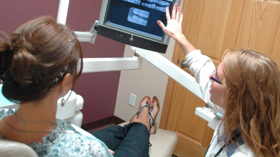 a dental professional goes over x-rays with a patient