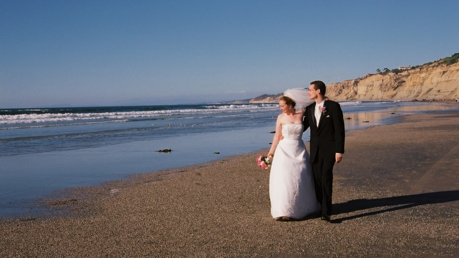a bride and groom on the beach